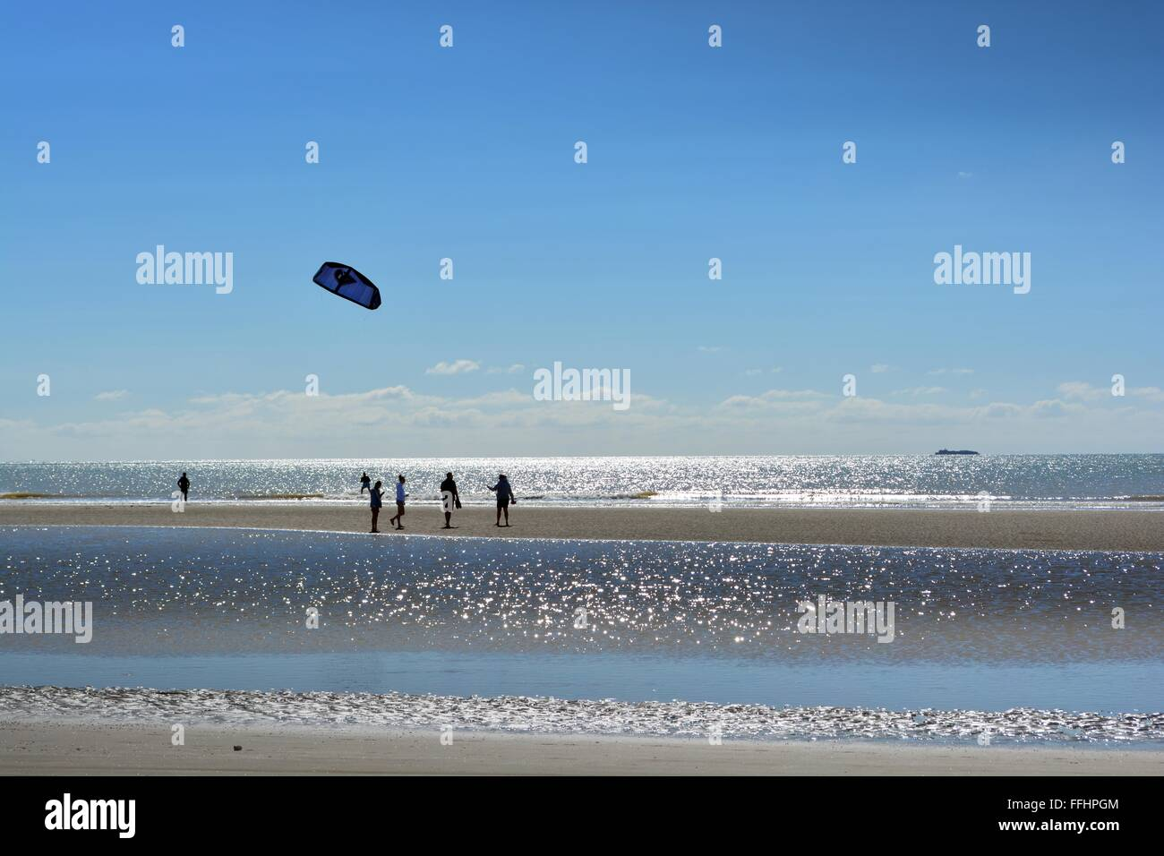 watching kite surfers at low tide above a sparkling sea in Camber Sands on the South coast, Sussex, UK - Stock Image