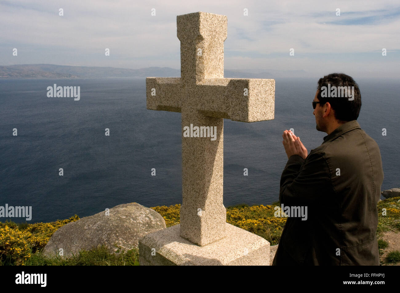 Way of St. James, Jacobean Route. Finis Terrae, Fisterre, Finisterre, A Coruña. Pilgrim pray at stone cross - Stock Image
