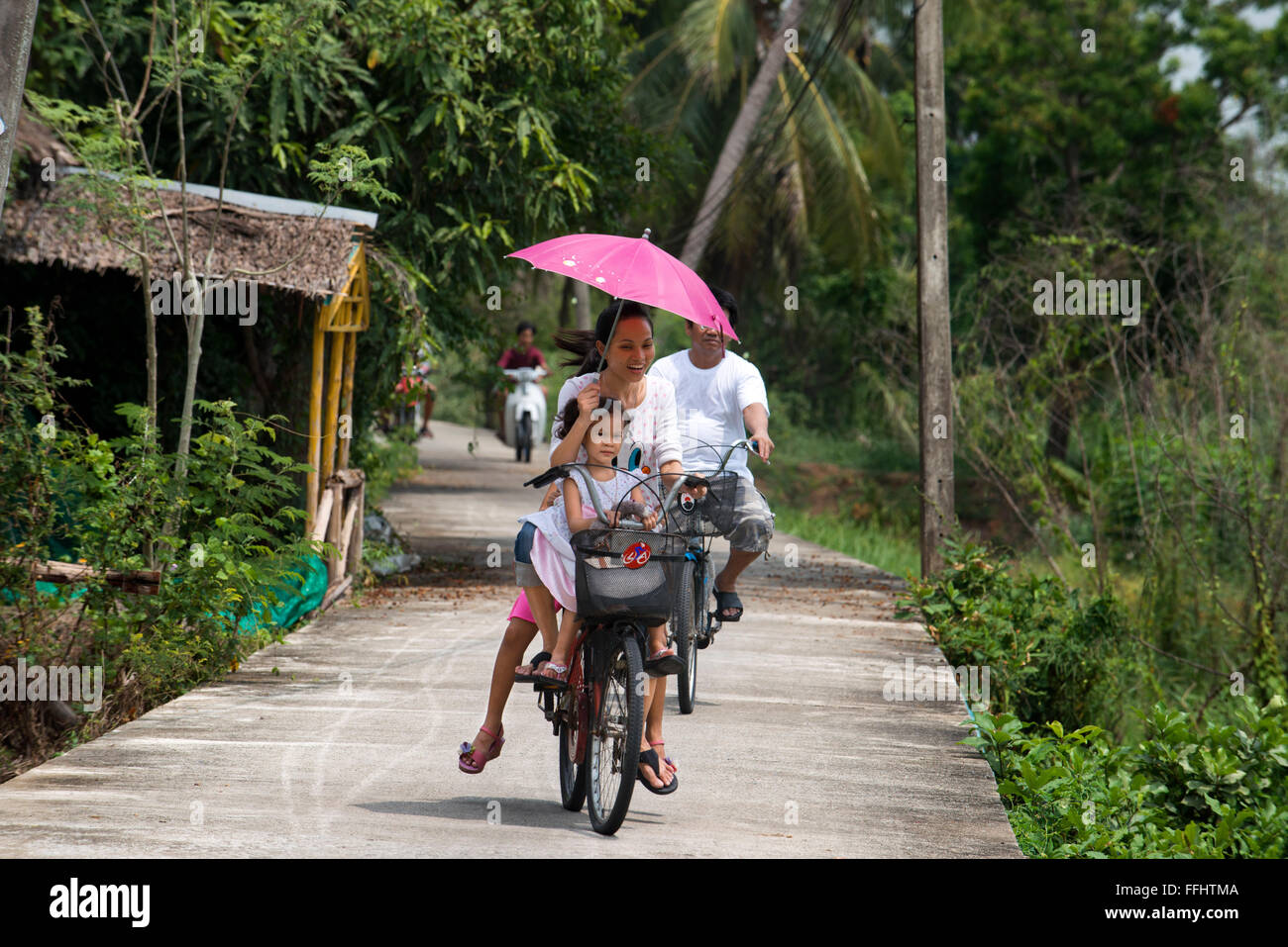 Asian tourists round the island by bicycle. Ko Kret (also Koh Kred) is an island in the Chao Phraya River, 20 km - Stock Image