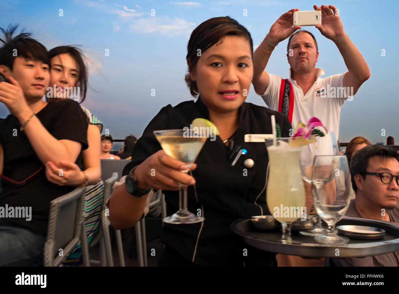 Waitress with cocktails in her hand. Banyan Tree Rooftop Vertigo & Moon Bar, Restaurant, , Bangkok , Thailand. - Stock Image
