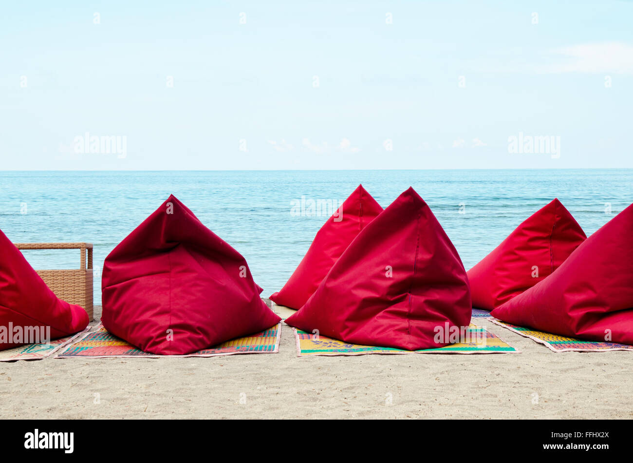 Red bean bags on the sand beach in Bali, Indonesia. Stock image. - Stock Image