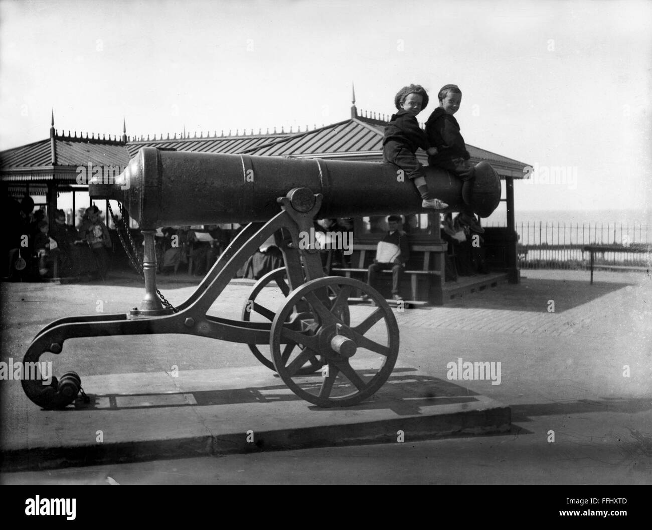 Victorian family boys sitting on cannon at Hastings Britain 1905 - Stock Image