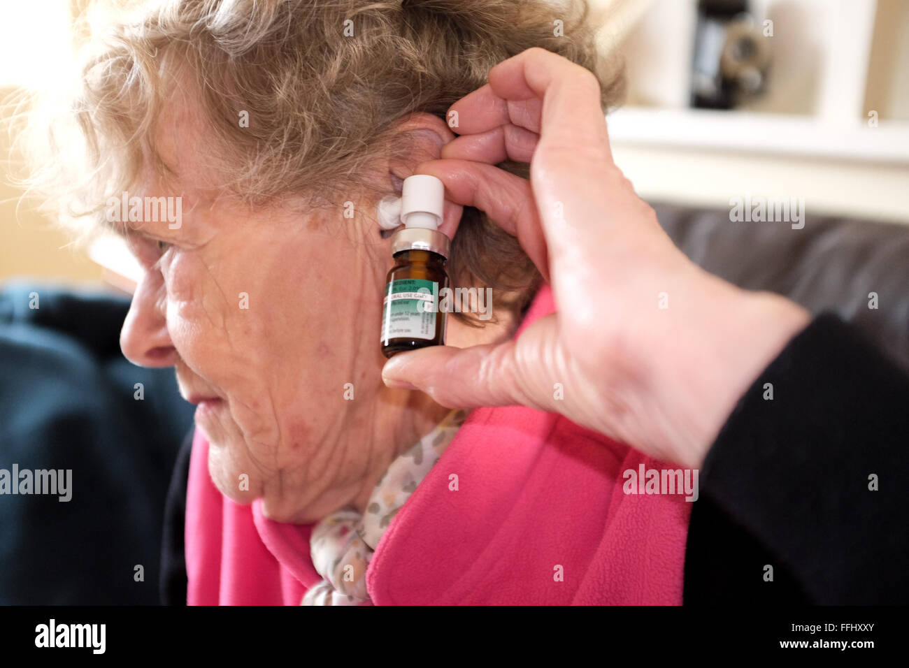 elderly woman using ear calm spray to help with an earache ear ache