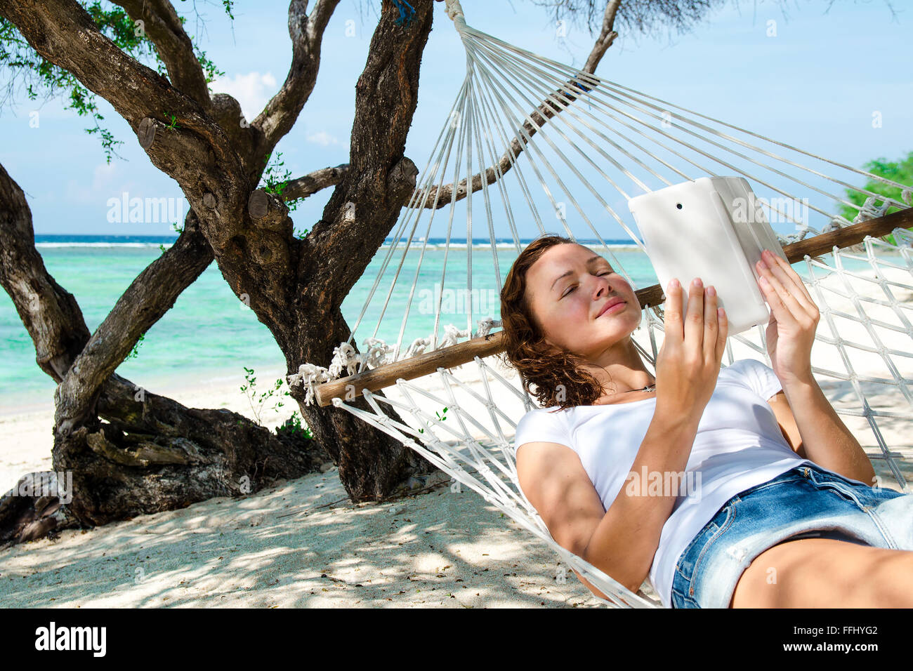 Woman in a hammock with laptop at the beach. Bali, Indonesia. Stock image. - Stock Image