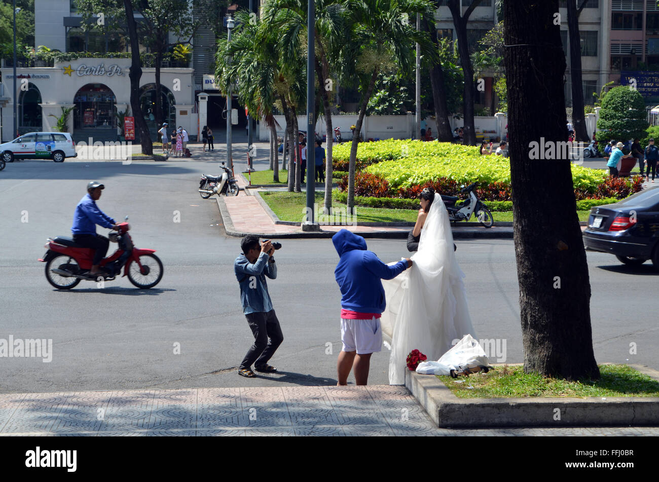A bride is posed in front of the Cathedral in the street to make an unusual setting for her wedding photos - Stock Image