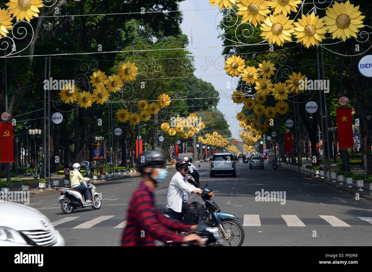 Saigon,VietNam.The streets gaily covered with bunting, flags, and these flowers as people get around onmotor bikes - Stock Image