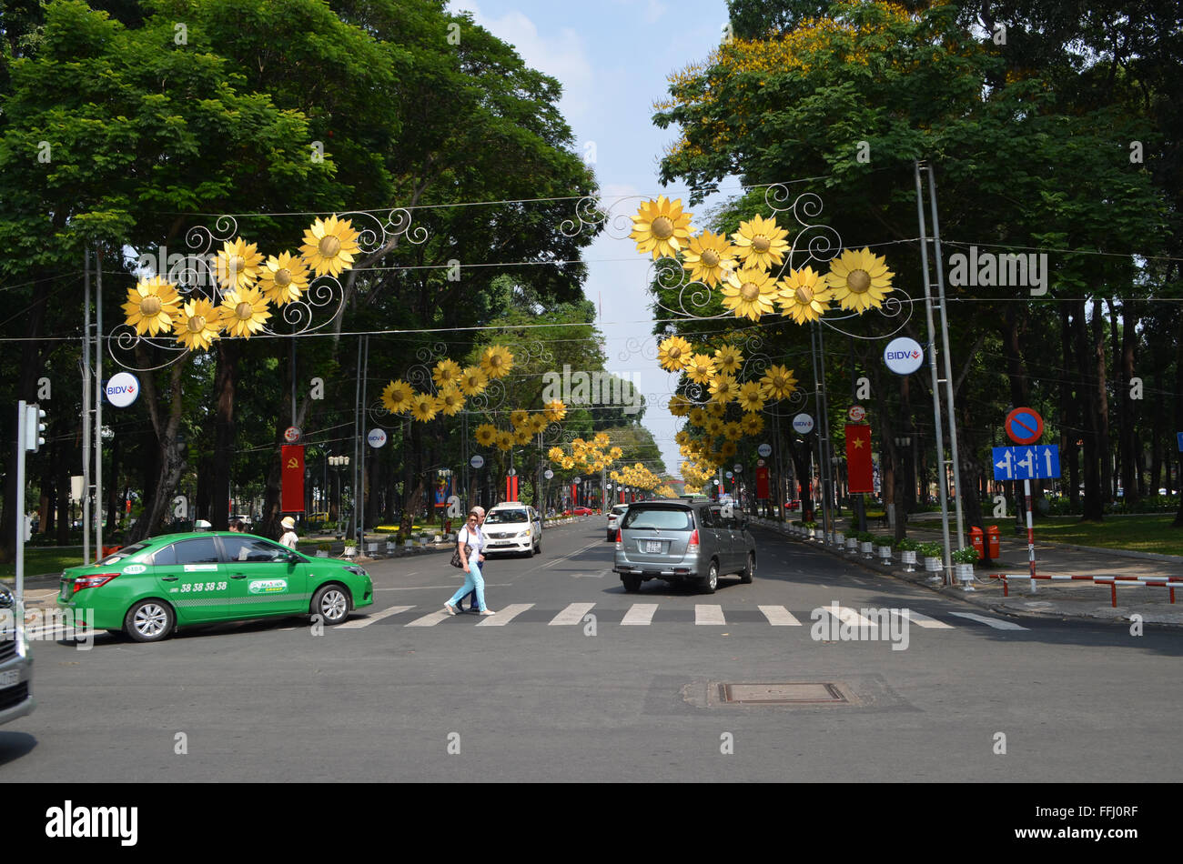 Saigon, VietNam The streets are gaily coveredwith bunting, flags, and these flowers as people travelon motorbikes - Stock Image