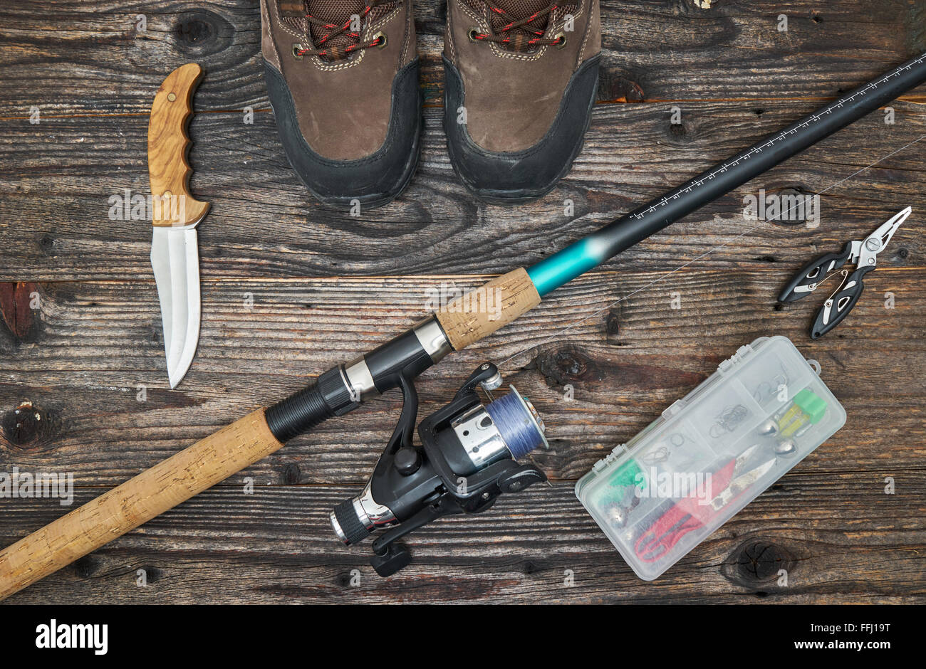 fishing tackles and fishing gear on wooden background, top view - Stock Image