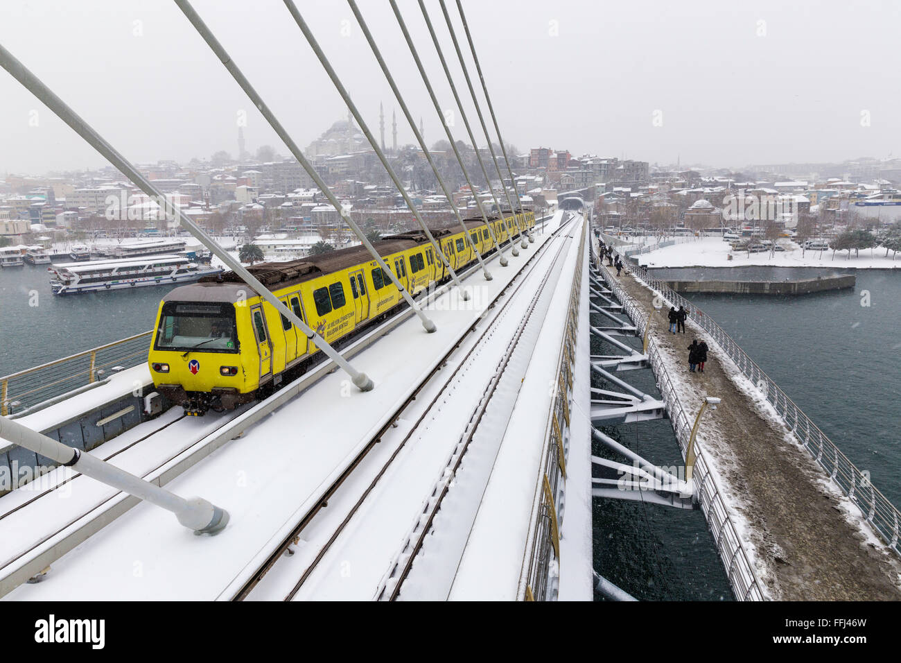 Istanbul subway metro train passing and people walking on the Golden Horn Metro Bridge on a snowy day near Halic - Stock Image