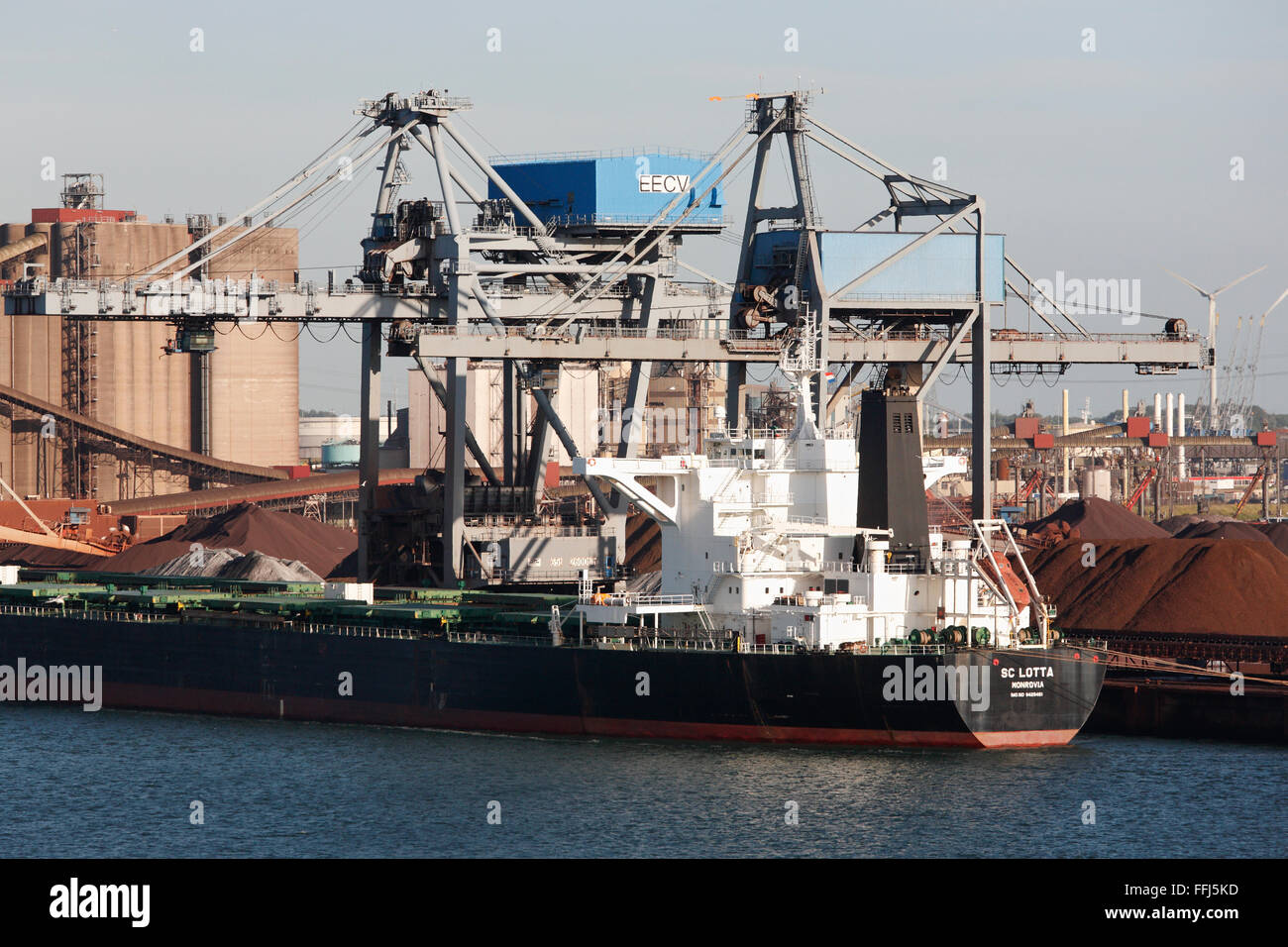 freighter SC Lotta Monrovia loading crude ore in the industrial harbour at Rotterdam, Netherlands - Stock Image