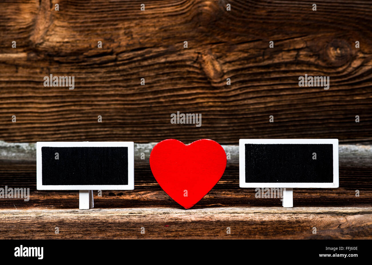 Red Wooden Heart And Two Small Blackboards On Very Old Wooden Board. Love Concept. - Stock Image
