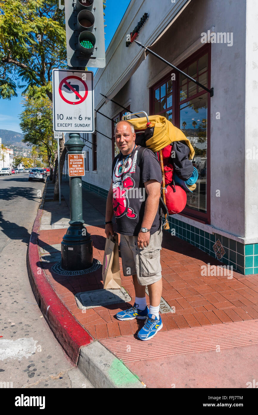 An older transient male backpacker carries his world possessions on his back as he walks up State Street in Santa - Stock Image