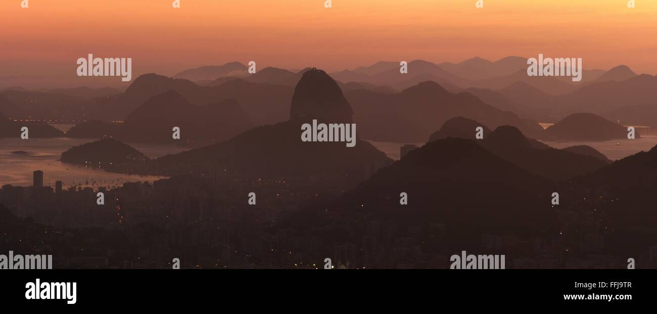 Rio de Janeiro, Brazil, 14th February. Rio de Janeiro at sunrise, seen from Vista Chinesa (Chinese Belvedere) in Tijuca Forest National Park. Sugarloaf is seen at centre.Stitched panorama. Credit:  Maria Adelaide Silva/Alamy Live News Stock Photo