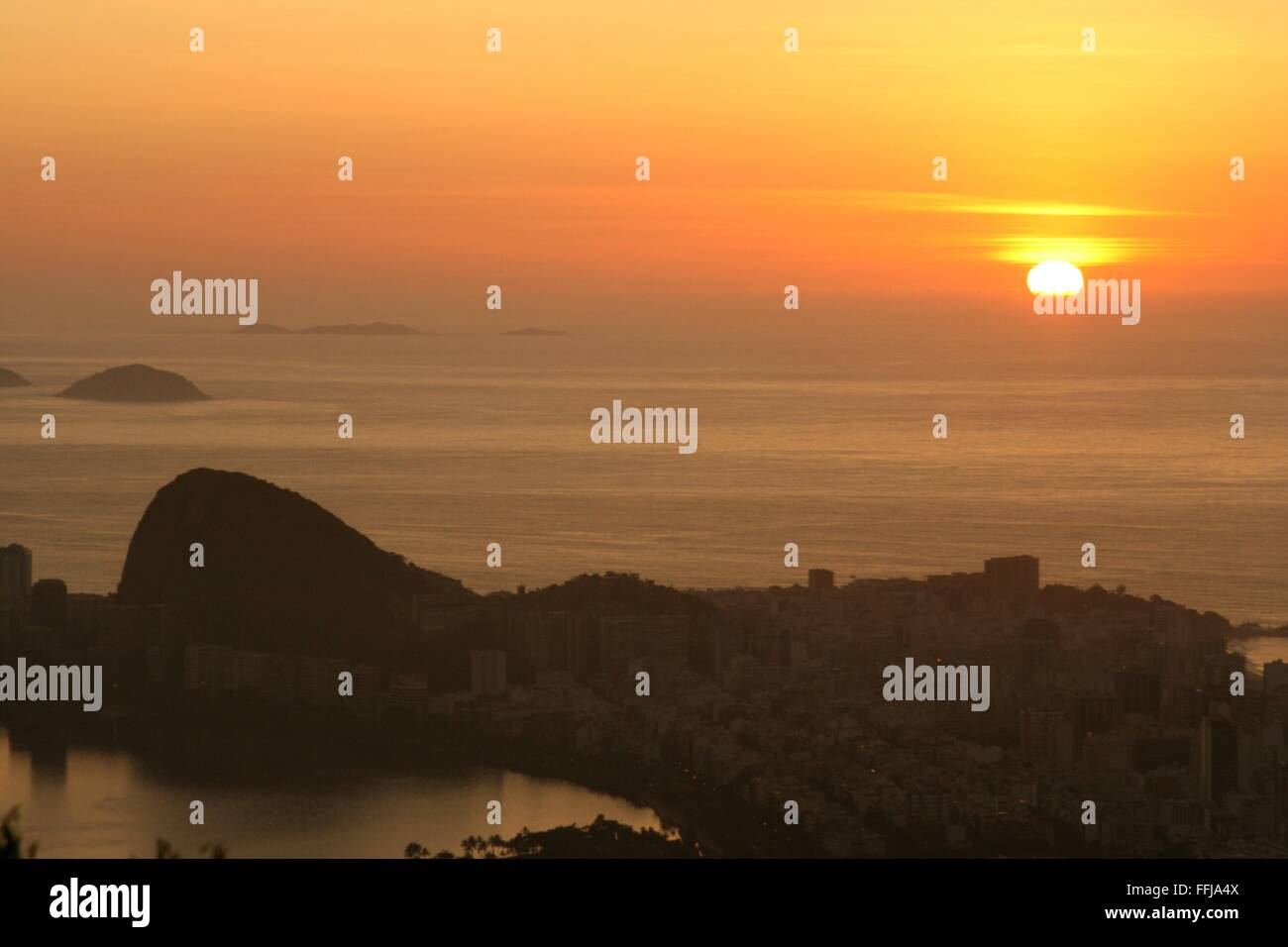 Rio de Janeiro, Brazil, 14th February. The sun rises in the sea, with Ipanema in the foreground, seen from Vista Stock Photo