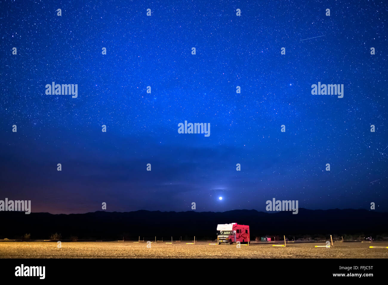 A starry sky over a lone RV parked at Stovepipe Wells Campground in Death Valley National Park, California - Stock Image