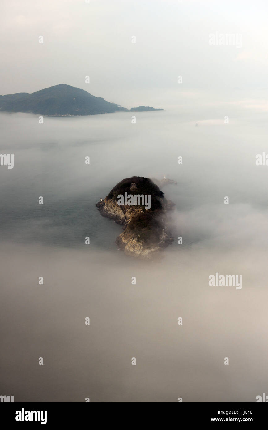 Low fogs covering the East Lamma Channel in Hong Kong. - Stock Image
