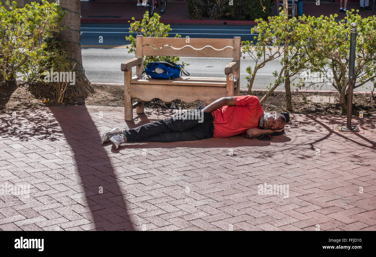 A middle-aged African-American homeless man sleeps sprawled out on the sidewalk on State Street in Santa Barbara, - Stock Image