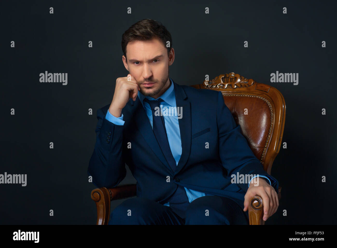 Confident businessman sitting in armchair - Stock Image