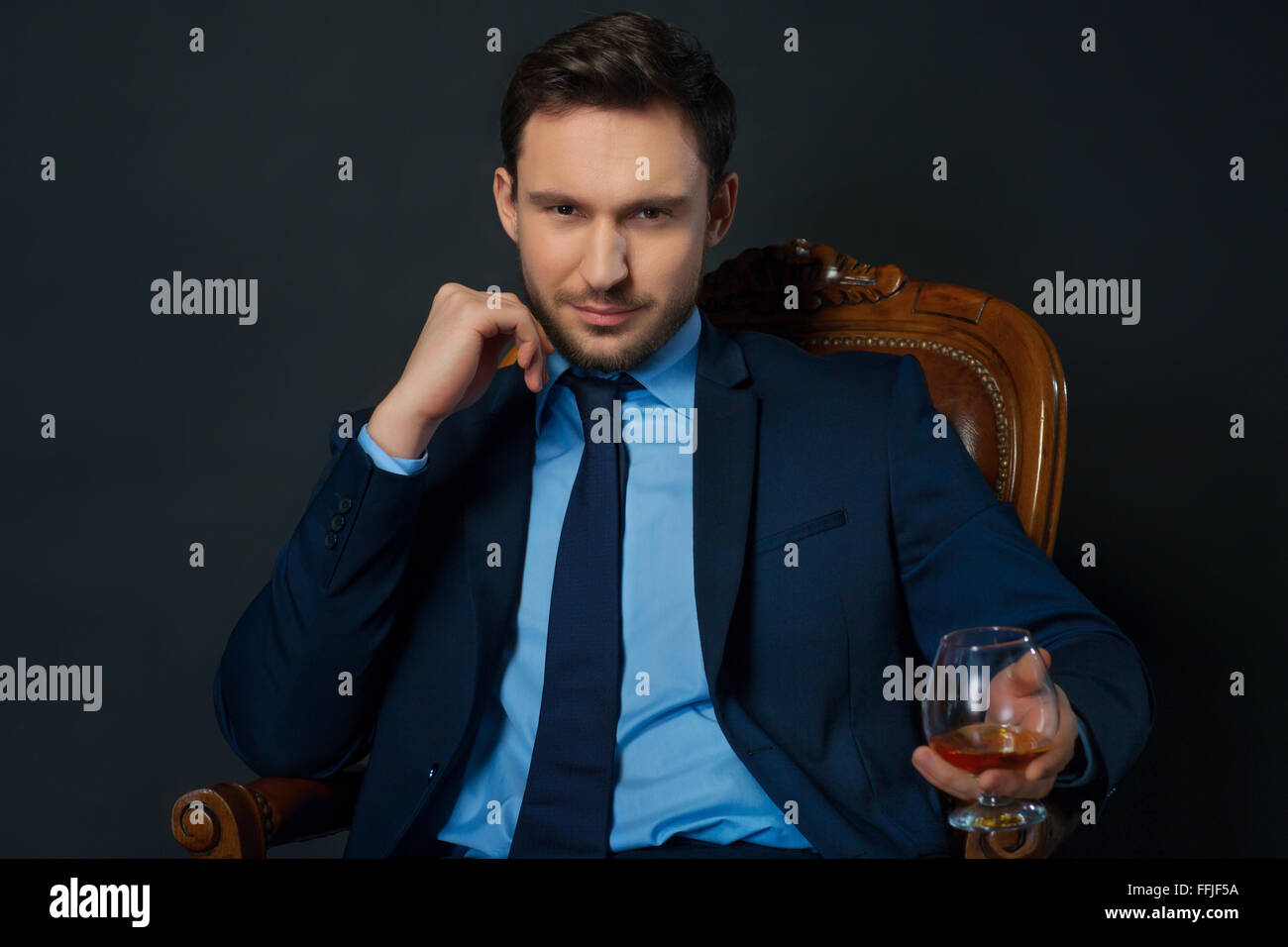 Handsome businessman drinking alcohol - Stock Image