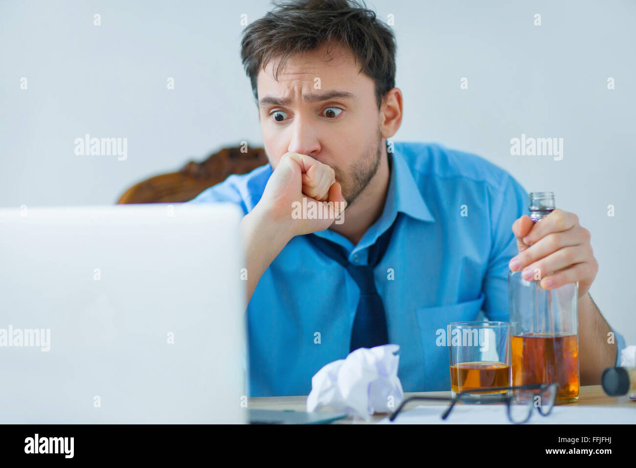 Drunk man drinking alcohol while working - Stock Image
