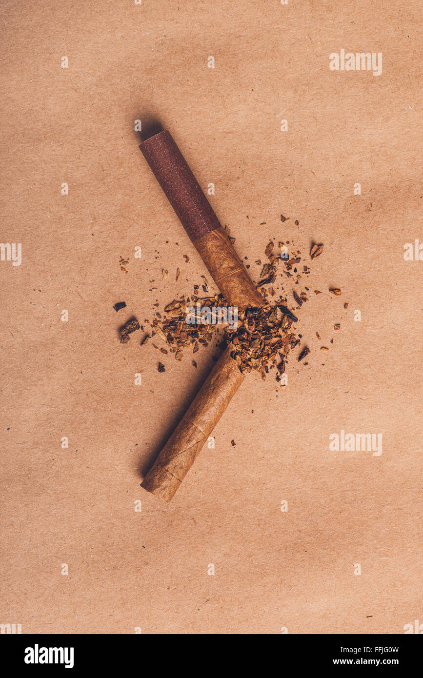 Broken cigarette top view over brown paper, quit smoking concept, warm retro vertical image tone. - Stock Image