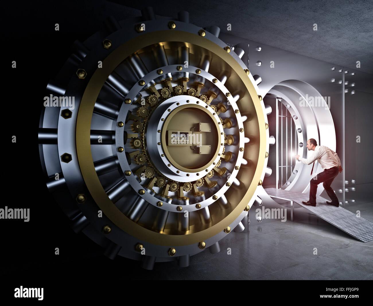 man with flashlight and vault bank door - Stock Image