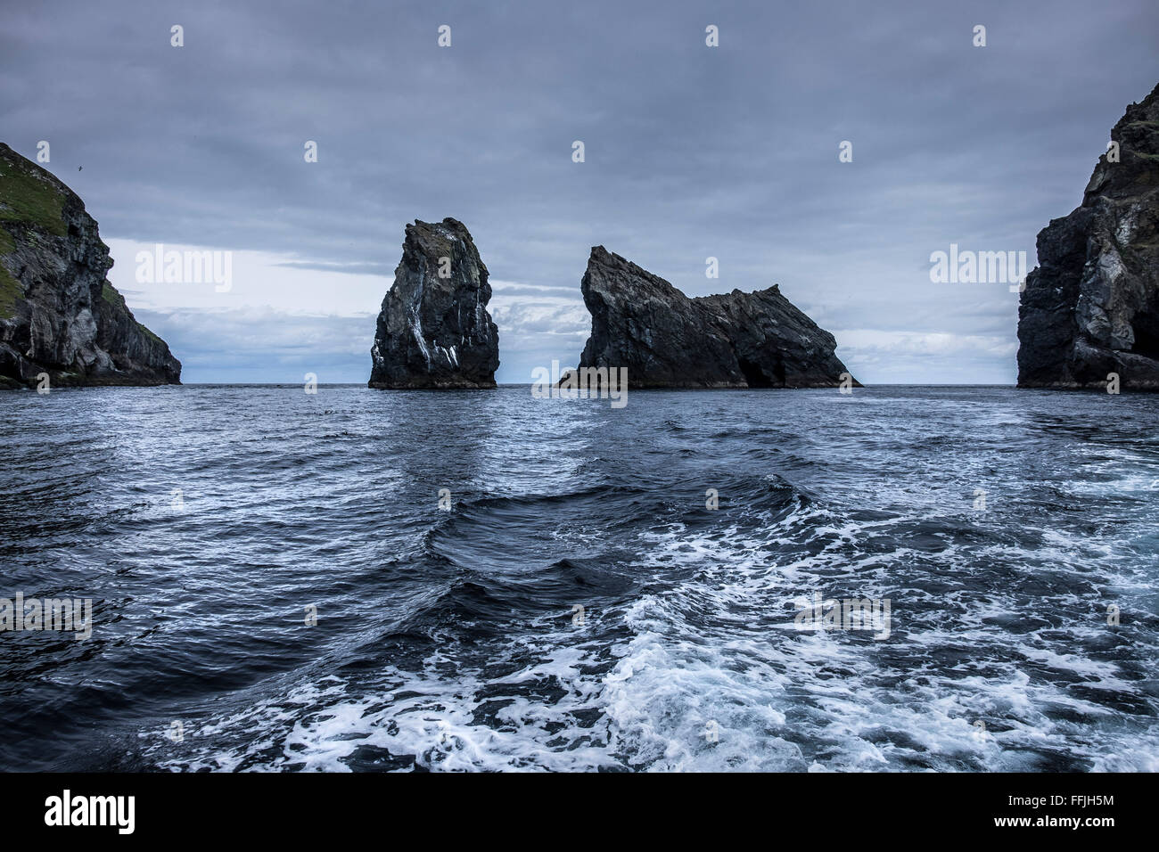 wake of motor boat with rocky outcrop in moody blue sea at st kilda - Stock Image