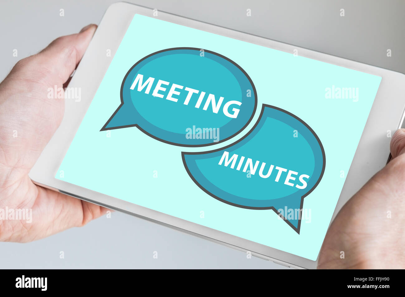 Meeting minutes concept with hands holding modern tablet or smartphone to be used as slide background - Stock Image