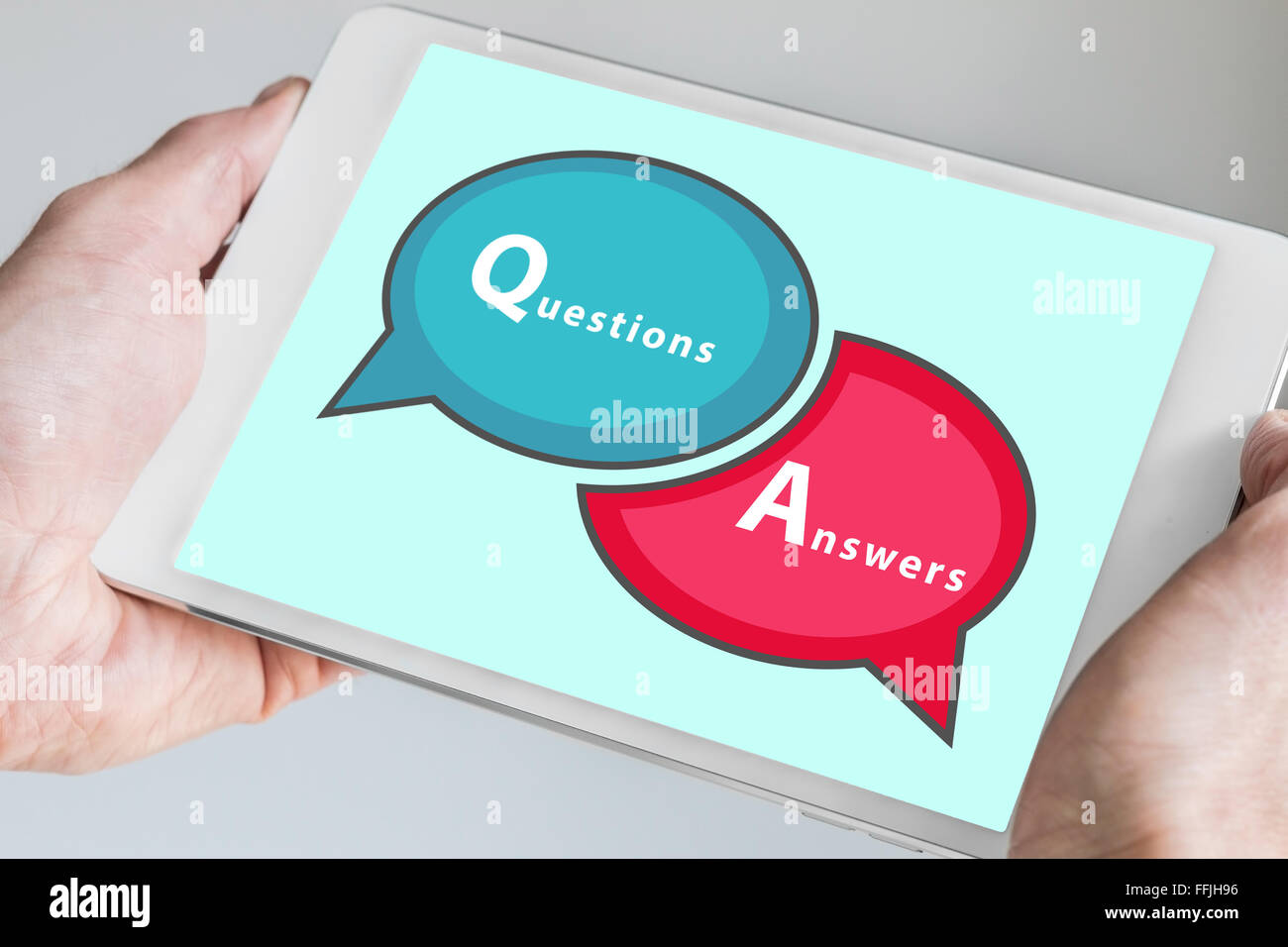 Questions and Answers Q&A session concept with hands holding modern tablet or smartphone to be used as slide - Stock Image