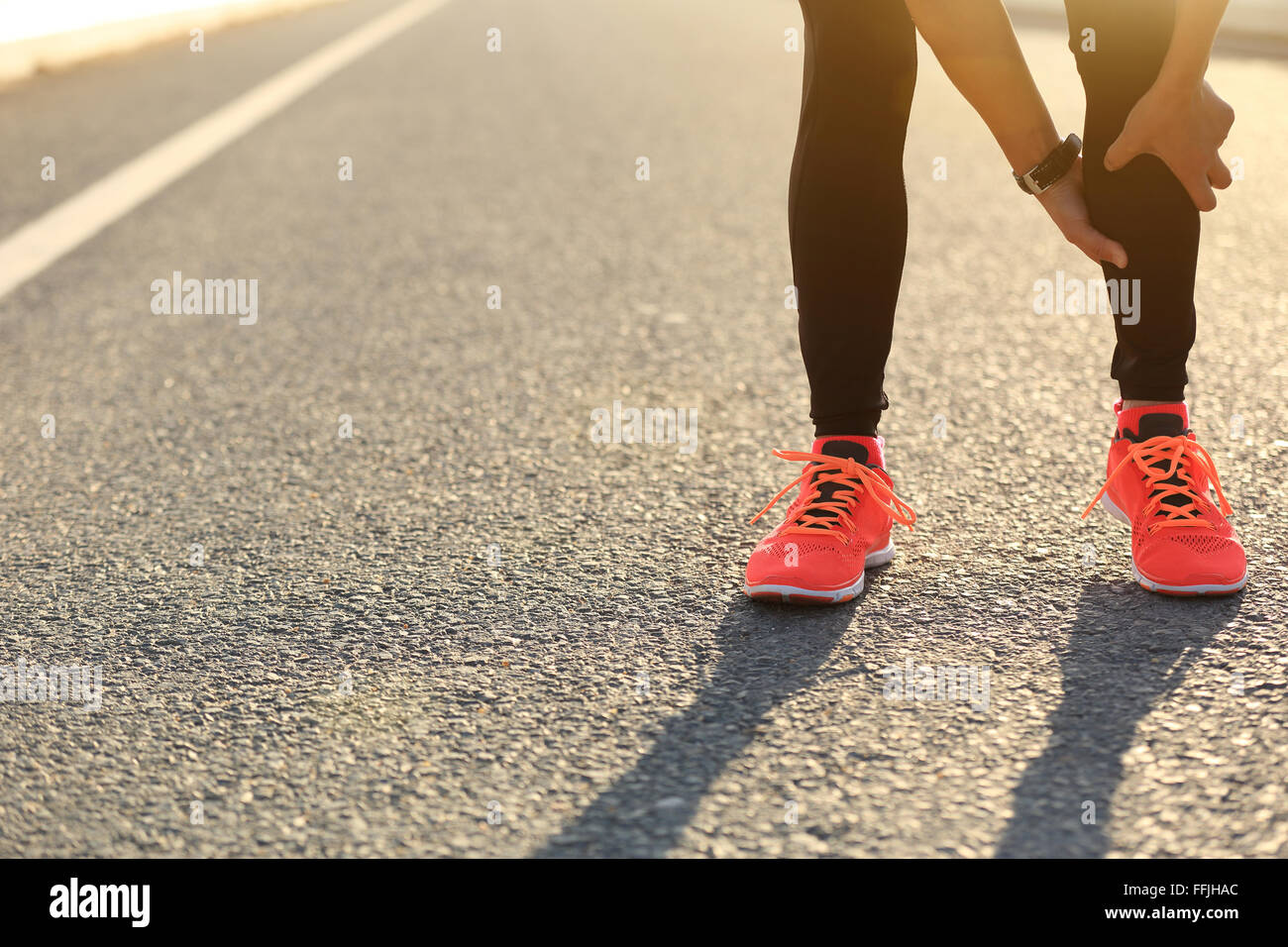 woman runner hold her injured leg on road - Stock Image