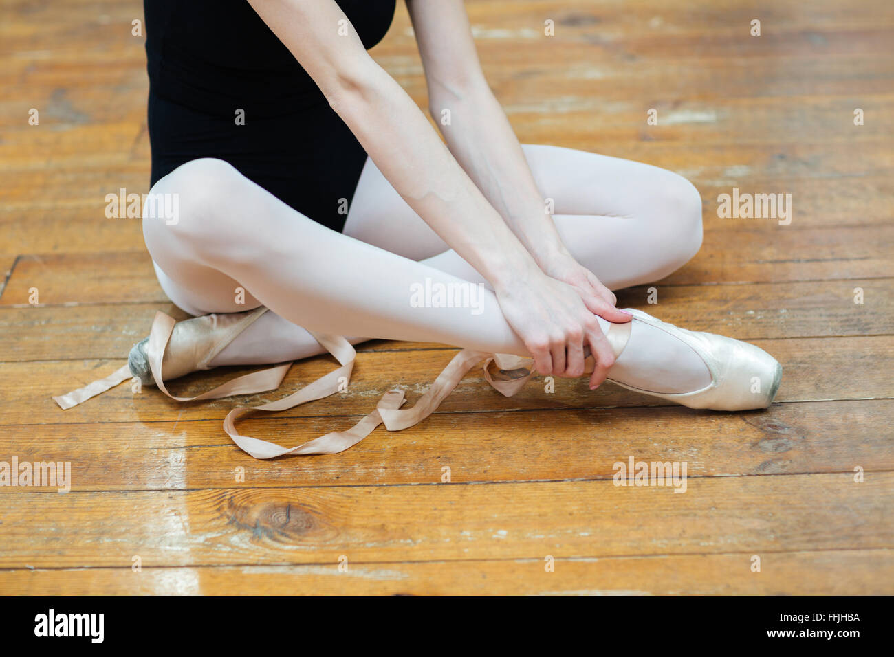 Cropped image of a ballerina in pointes having pain in ankle - Stock Image