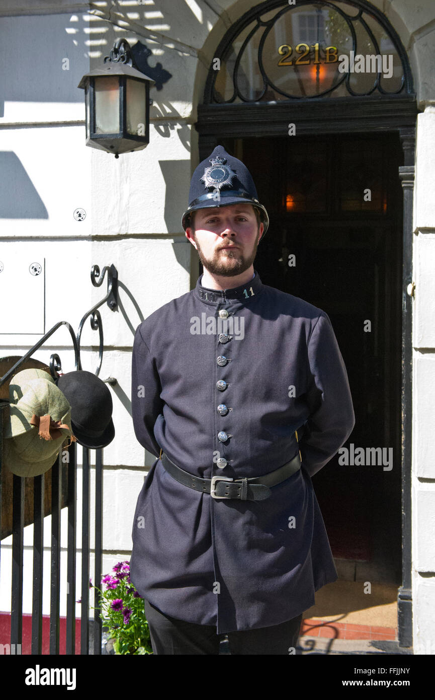 A man in costume (old Police uniform) outside the famous Sherlock Holmes Museum in Baker Street, London, United - Stock Image