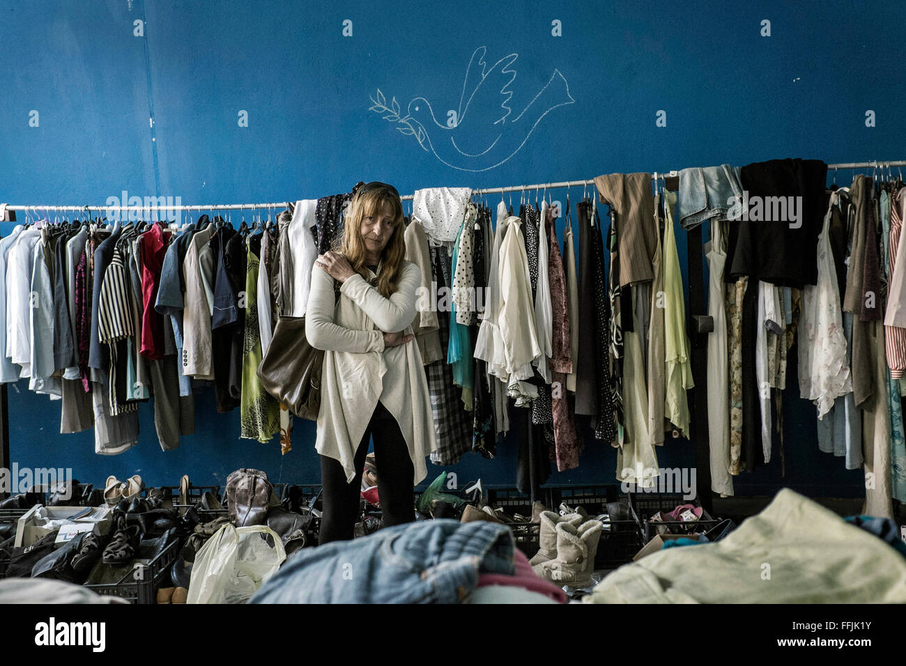 Matina stands in the cloth storage she organised for the refugees in Leros. Matina is a former judge and the initiator - Stock Image