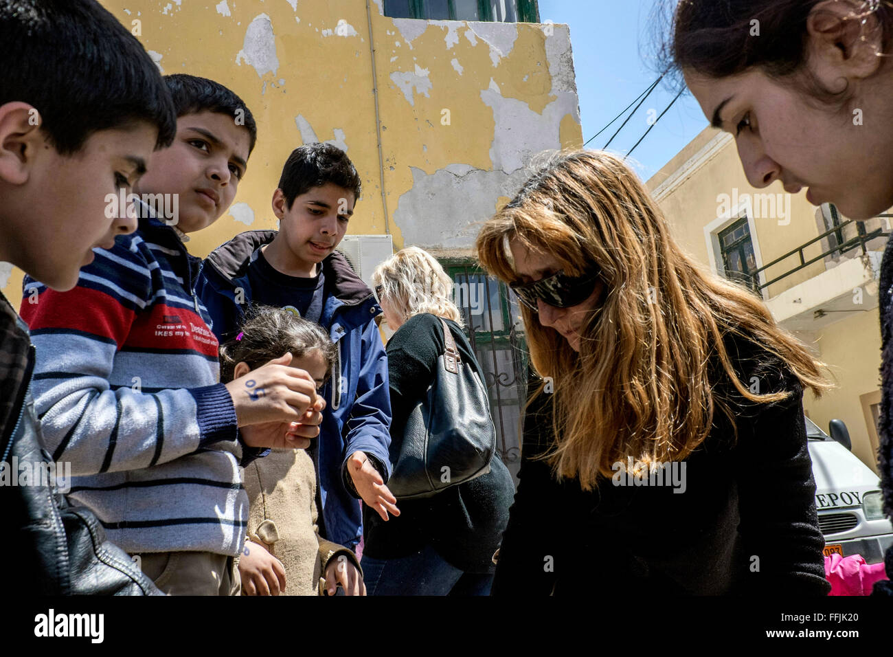 Matina distributes clothes to the refugees in Leros. Matina is a former judge and the initiator of the solidarity - Stock Image