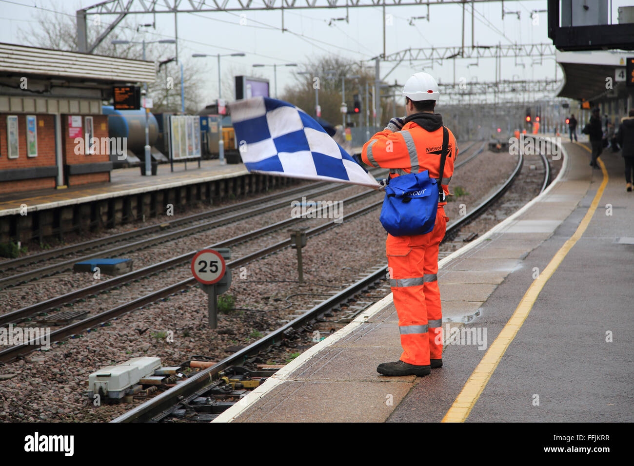 Railway worker wearing high visibility orange clothing holds blue and white checkered safety flag, Colchester, Essex, - Stock Image