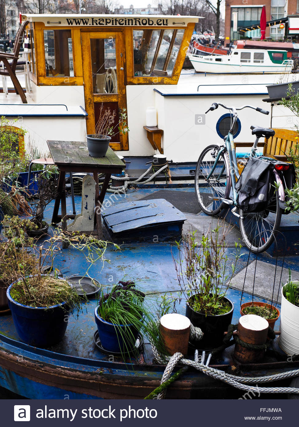 Bicycle on canal house boat, Amsterdam - Stock Image