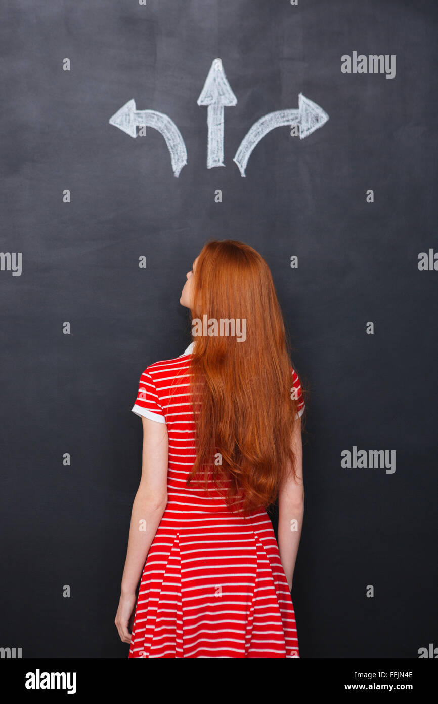 Back view of young woman with long red hair standing and choosing direction over chalkboard background - Stock Image