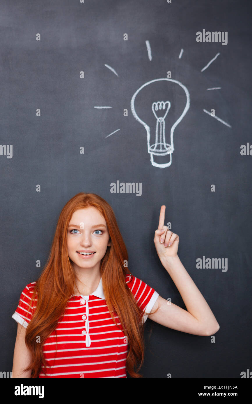 Attractive inspired young woman with red hair pointing up and having an idea over blackboard background - Stock Image