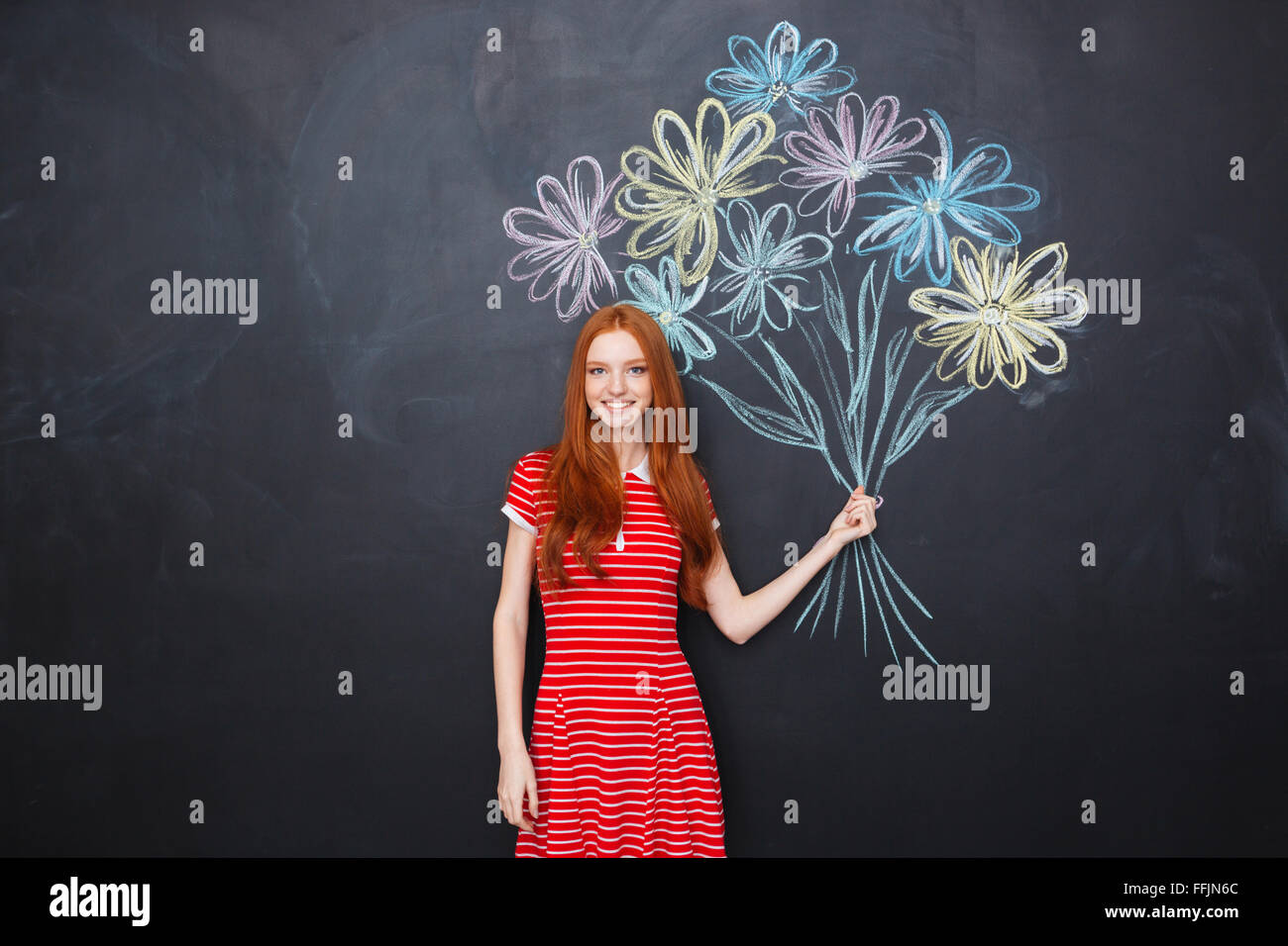 Smiling attractive redhead young woman standing and holding bouquet of drawn flowers over blackboard background - Stock Image