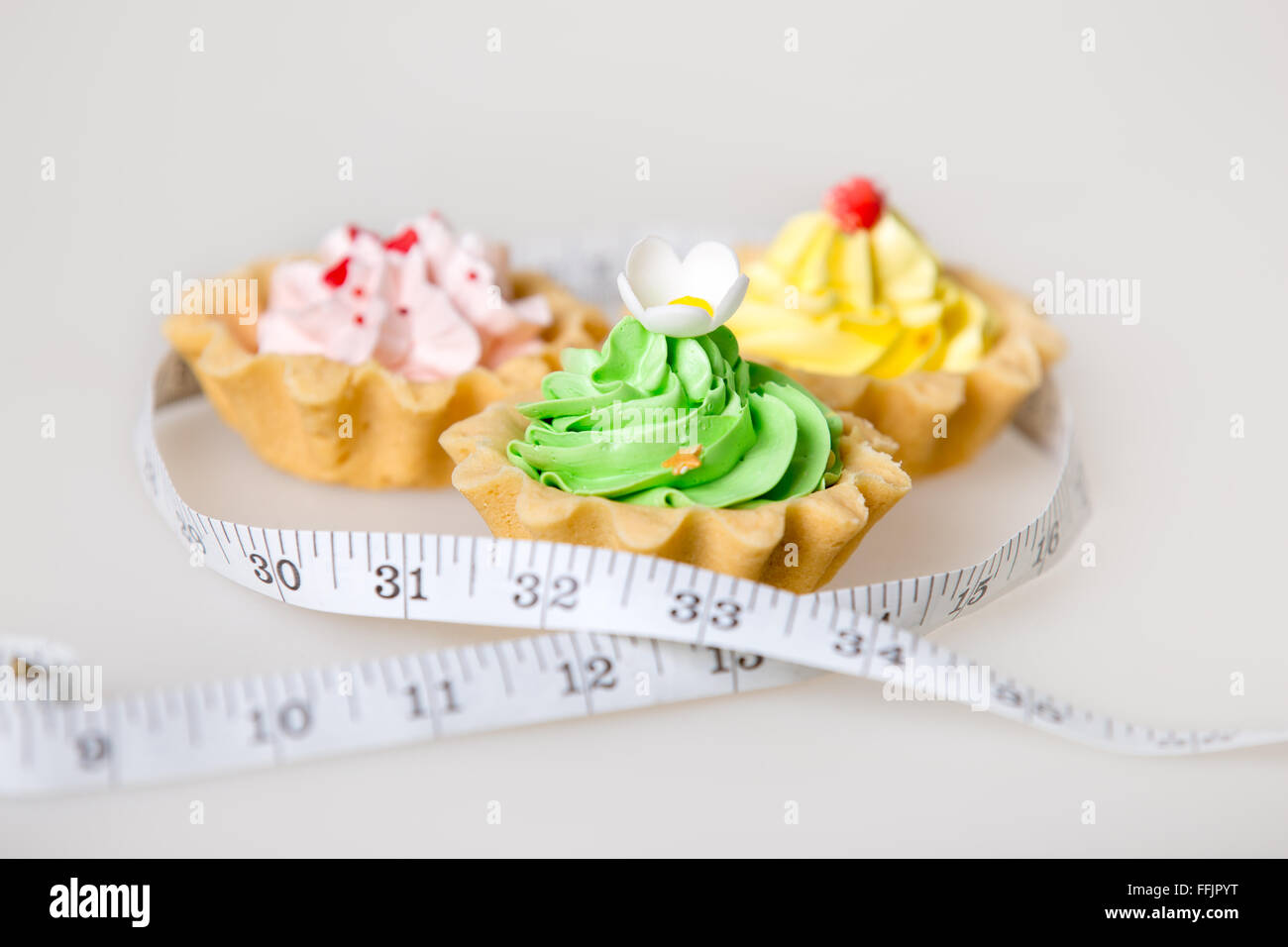 Three colorful green, pink and yellow tart cakes wrapped in measuring tape on white background, unhealthy lifestyle - Stock Image
