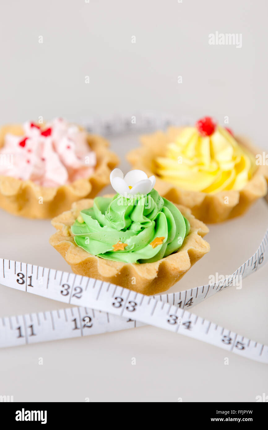 Three colorful tart cakes wrapped in measuring tape on white background, weight loss concept, studio - Stock Image