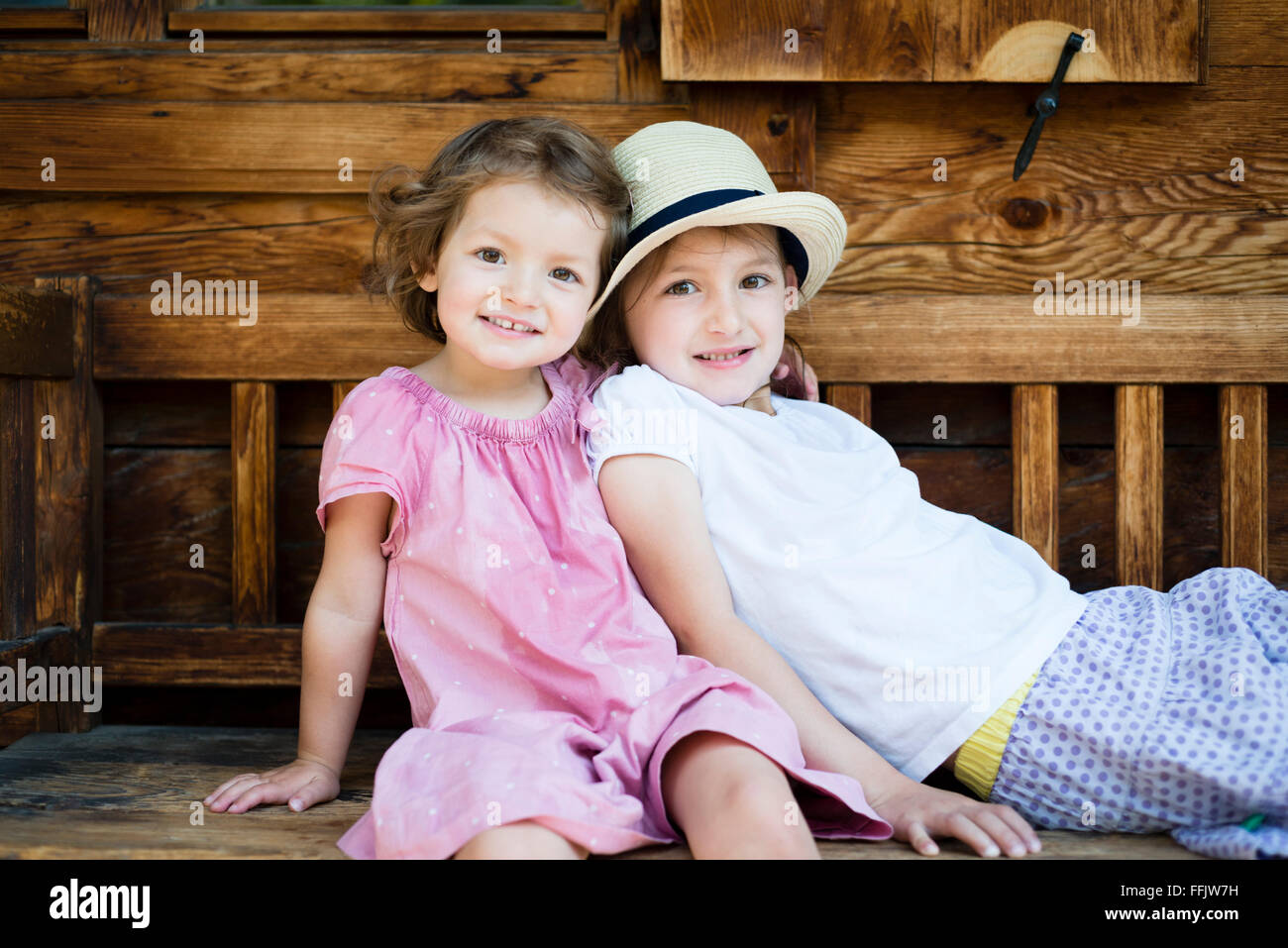 Portrait of two little girls on bench - Stock Image