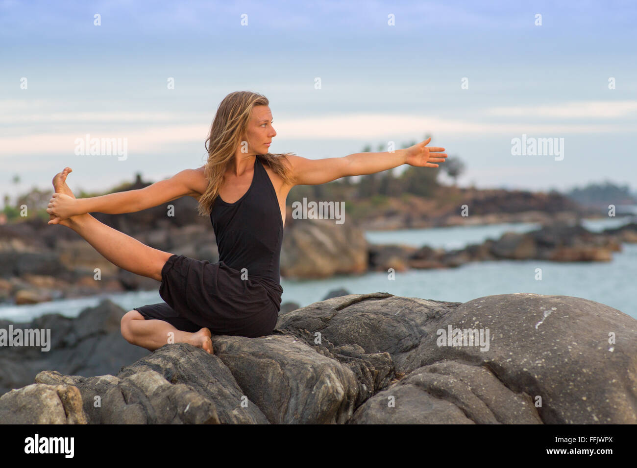 Yoga girl by ocean - Stock Image