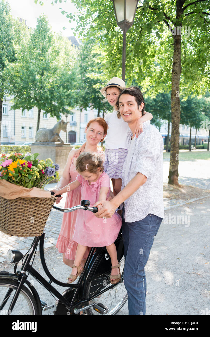 Family with two children pushing bicycle in city - Stock Image