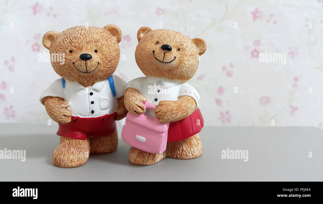Couple Of Ceramic Bear Dolls In School Uniform Go To School On Blurred Pink  Flower Wallpaper Background