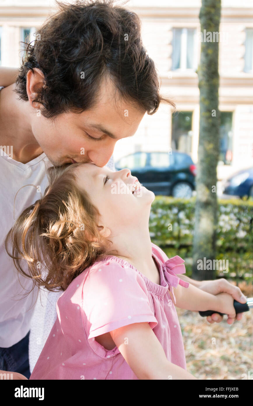 Father kissing daughter's forehead - Stock Image