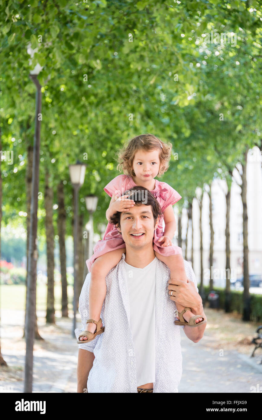 Father carrying daughter on his shoulders - Stock Image