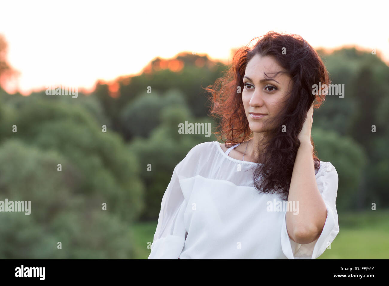 Young happy woman with black frizzy hair standing outdoors against woods in the evening. Portrait of hispanic smiling - Stock Image