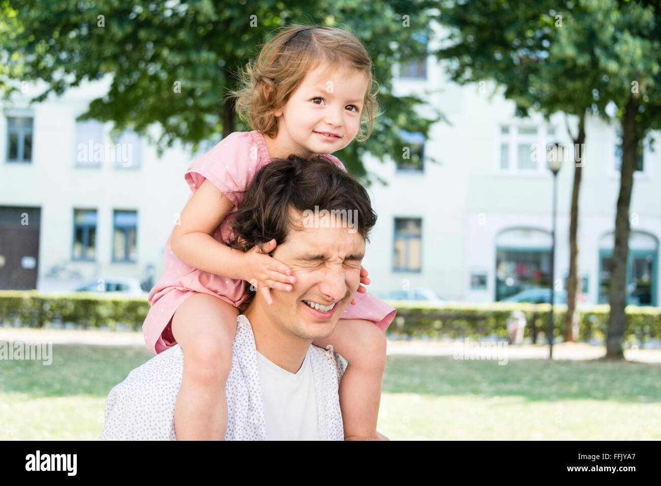 Father carrying daughter on shoulders - Stock Image