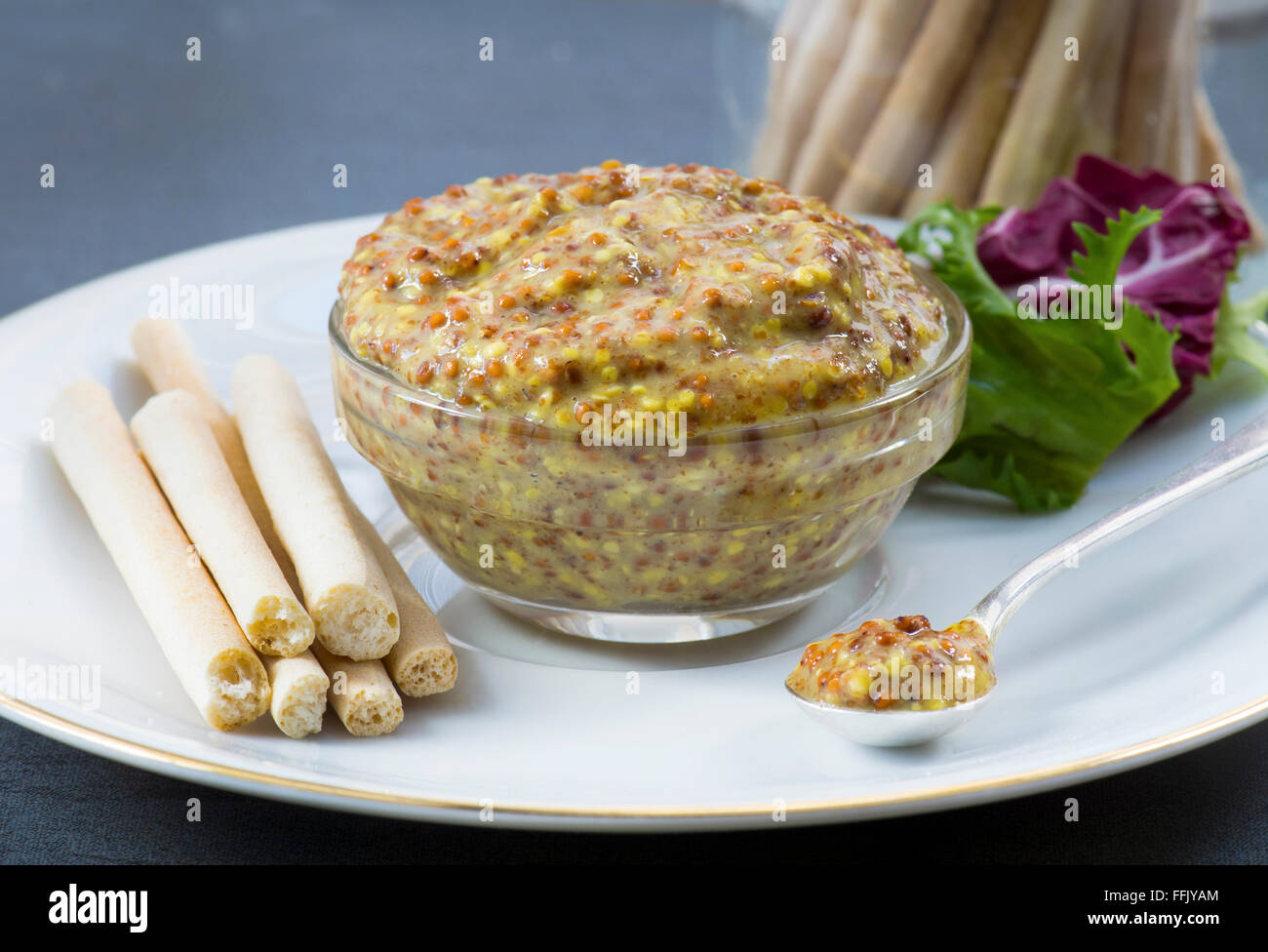 Mustard in a glass dish with a silver spoon on a white bone china plate, with bread stick and salad. Shot with a - Stock Image